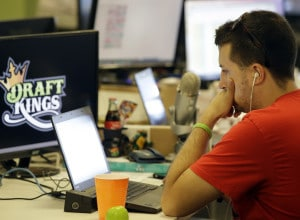 In this Wednesday, Sept. 9, 2015, photo, Devlin D'Zmura, a tending news manager at DraftKings, a daily fantasy sports company, works on his laptop at the company's offices in Boston. The daily fantasy sports industry is eyeing a breakout season as NFL games begin. And its two dominant companies, DraftKings and FanDuel, are touting lucrative opening week prizes to try to draw more customers as more competitors pop up. (AP Photo/Stephan Savoia) ORG XMIT: MASS203