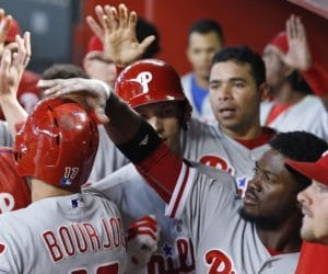 Philadelphia Phillies' Odubel Herrera, second from right, slaps the helmet of Peter Bourjos (17) after Bourjos scored against the Arizona Diamondbacks during the 10th inning of a baseball game Wednesday, June 29, 2016, in Phoenix. The Phillies defeated the Diamondbacks 9-8. (AP Photo/Ross D. Franklin)