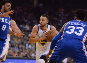 The Golden State Warriors' Stephen Curry (30) splits the Philadelphia 76ers' Jahlil Okafor (8) and Robert Covington (33) as he drives to the basket in the first half of their NBA game at Oracle Arena in Oakland, Calif., on Tuesday, March 14, 2017. (Dan Honda/Bay Area News Group)