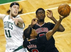 Chicago Bulls' Rajon Rondo (9) goes up to shoot in front of teammate Bobby Portis and Boston Celtics' Kelly Olynyk (41) during the second quarter of a first-round NBA playoff basketball game Sunday, April 16, 2017, in Boston. (AP Photo/Michael Dwyer)